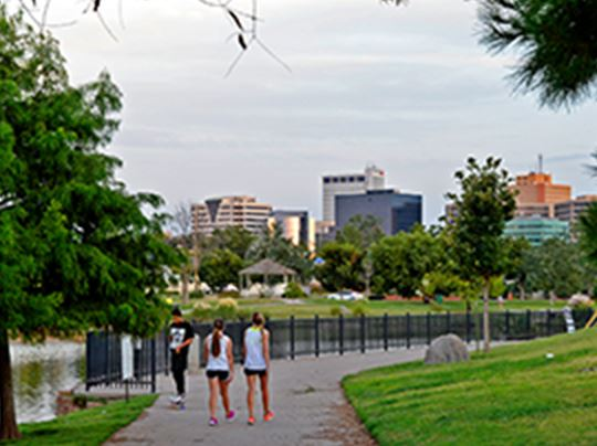 People walking on sidewalk near pond with city in background