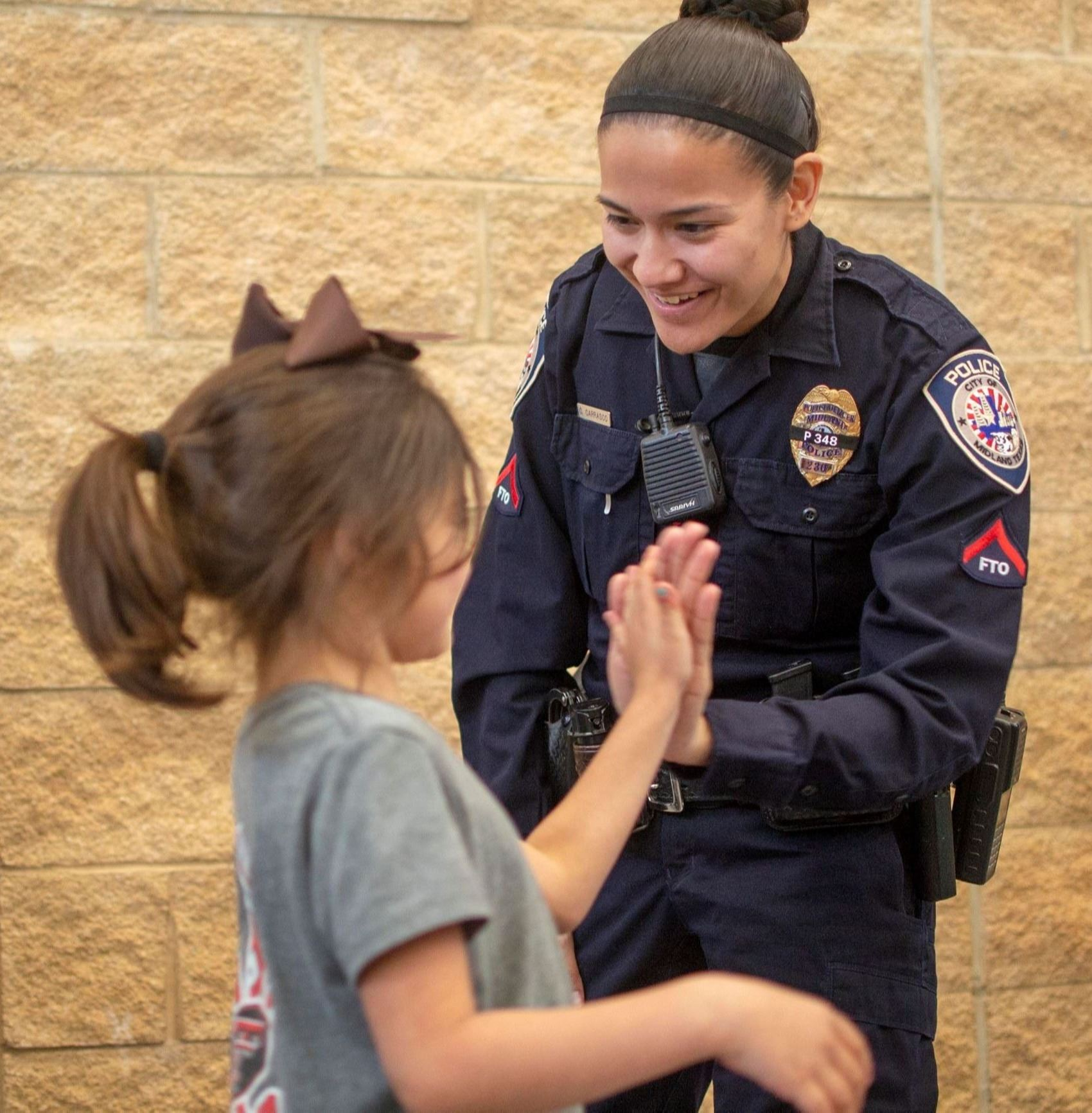 A photo of a police officer high-fiving a child